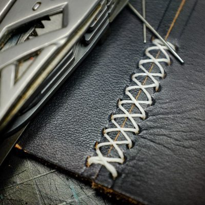 Hand-sewing two leather pieces with a cross stitch pattern