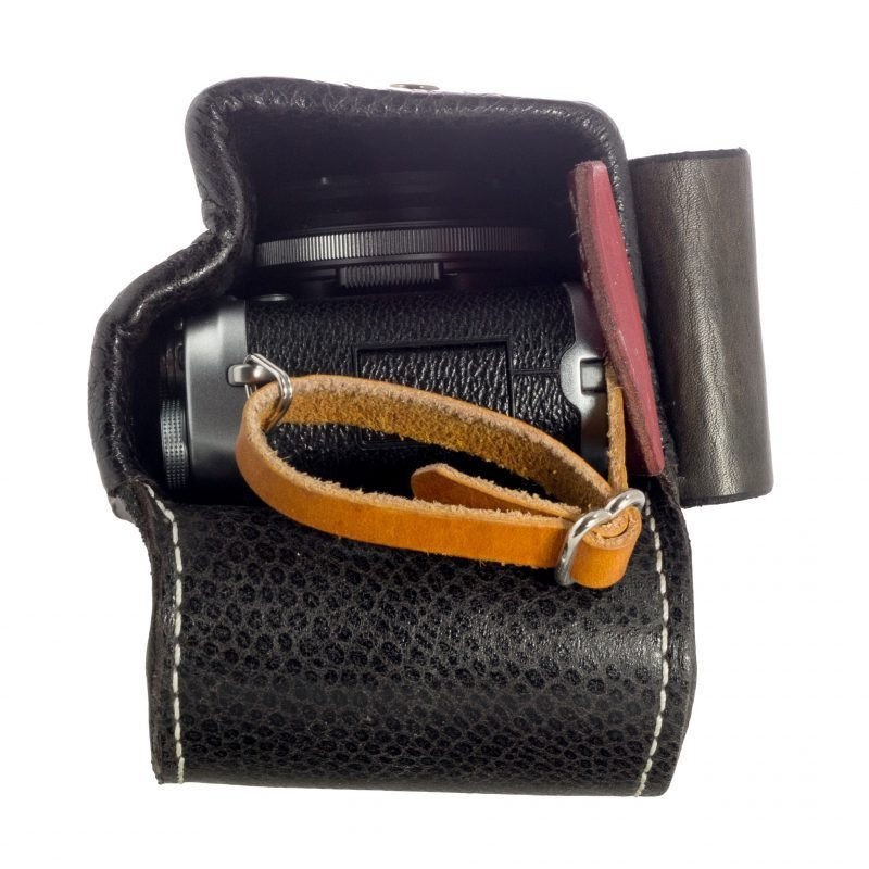 The camera fits snugly (without lens hood). The inside is lined with patterned leather (this is not snake). The smooth surface of the lining makes it easier to slide the camera in and out.